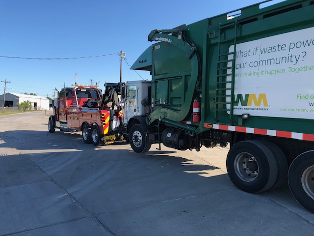 Image of a Waste Management truck being towed
